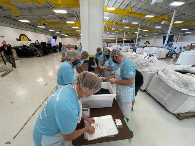 Volunteers from the Oshkosh Corporation help fill bags of beans and rice for Feeding America Eastern Wisconsin on Sept. 16, 2021. (WFRV)